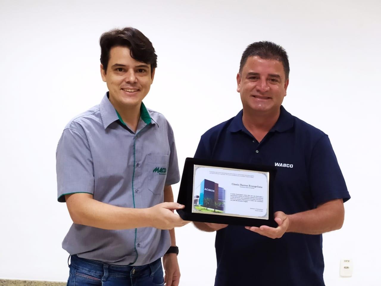 Foto: Eduardo Drumond entregando placa de homenagem ao Cássio Barros.